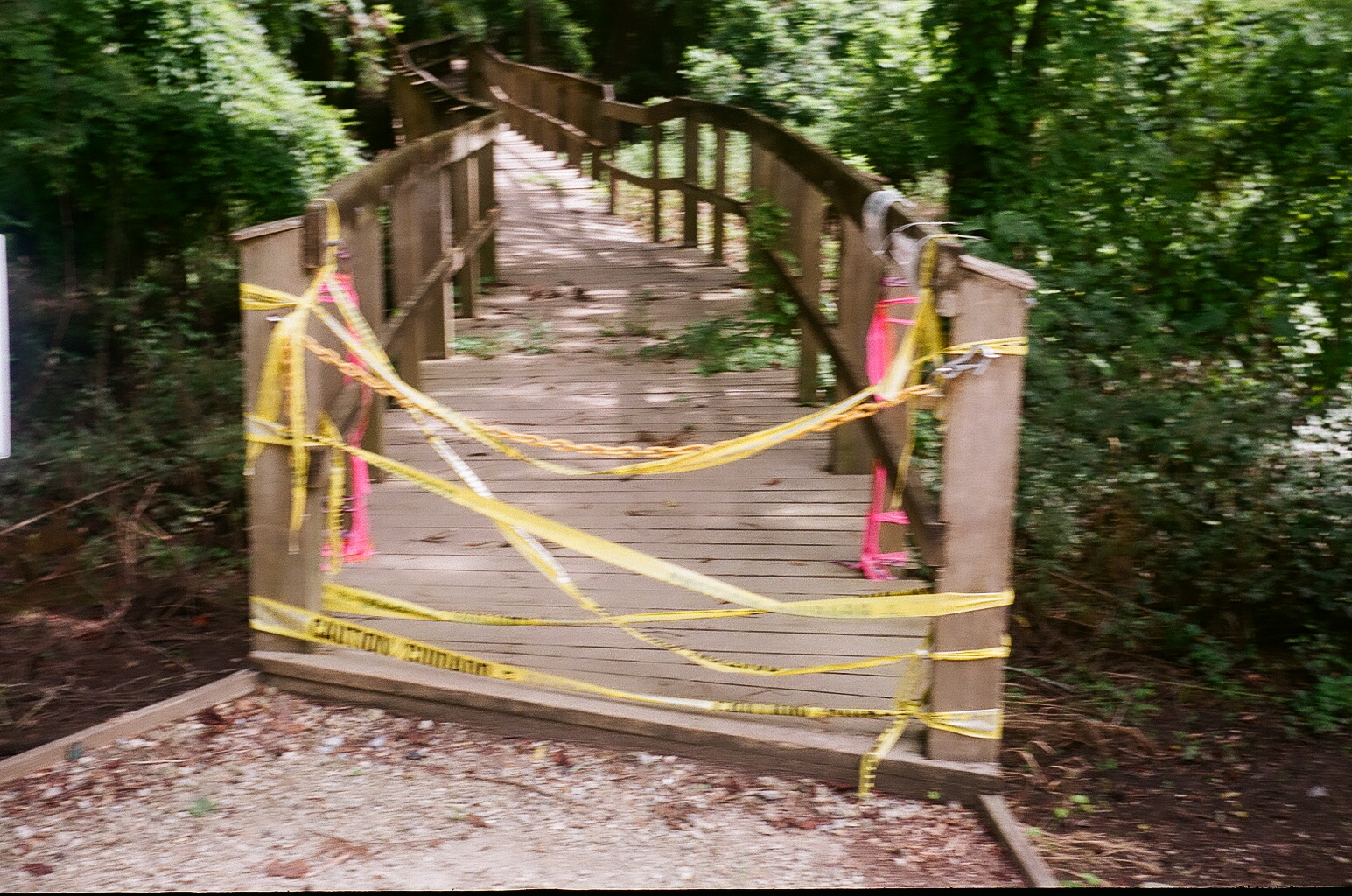 A blurry shot of a walkway blocked with Caution tape
