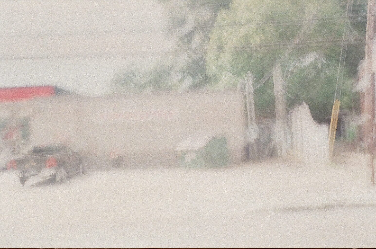 A photo of a gas station dumpster, also overexposed and blurry