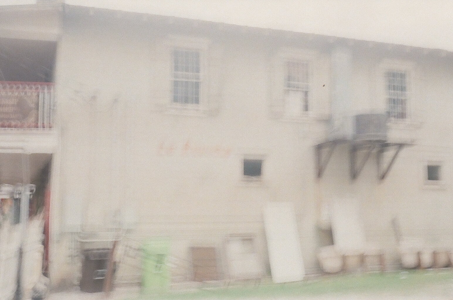 An attempted photo of a hand painted sign on the side of an antique store